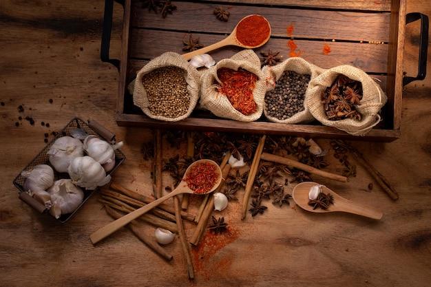 Conjunto de vista superior de especiarias e ervas na bandeja de madeira, alimentos e ingredientes da culinária. Foto Premium