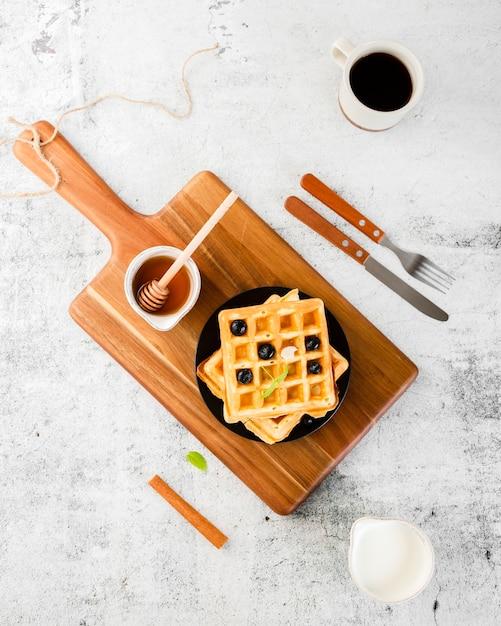 Conjunto de vista superior de waffle em cima de madeira Foto gratuita