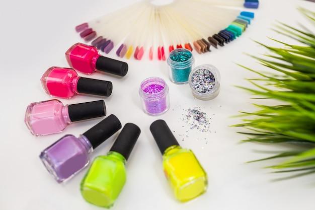 Conjunto para o design de manicure: muitos esmaltes coloridos e brilhos / brilhos em close-up da mesa branca. Foto Premium
