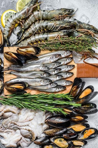Conjunto variado de camarões tigre de frutos do mar frescos, camarões, mexilhões azuis, polvos, sardinhas, cheiros Foto Premium