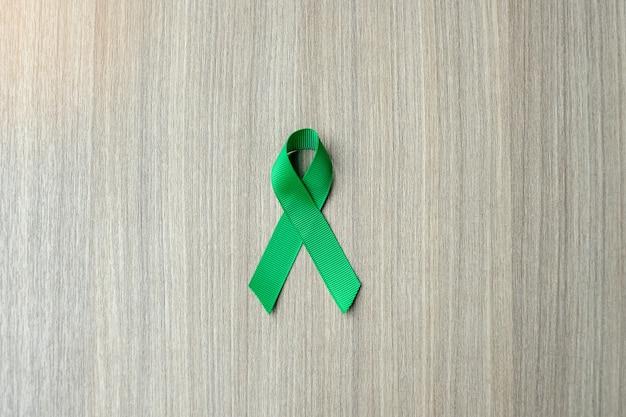 Conscientização do câncer de fígado, fita verde sobre fundo de madeira Foto Premium