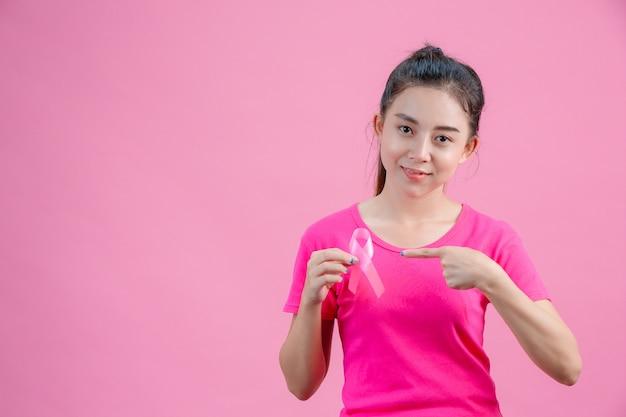 Conscientização do câncer de mama, mulheres vestindo camisas cor de rosa a mão direita segura uma fita rosa. a mão esquerda apontada para a fita que mostra o símbolo diário contra o câncer de mama Foto gratuita