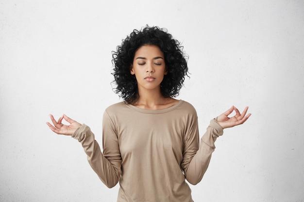 Consideração e oração. calma linda jovem negra com penteado afro, mantendo os olhos fechados enquanto pratica ioga dentro de casa, meditando, de mãos dadas no gesto mudra, pensando em paz Foto gratuita