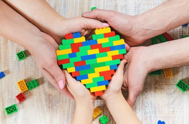 Construa um coração de lego designer. fundo seletivo. Foto Premium
