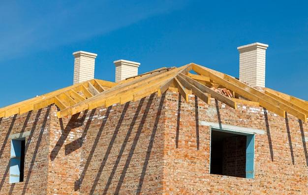 Construção de coberturas. estrutura de telhado de madeira, chaminés brancas e construção de casas de tijolos amarelos Foto Premium