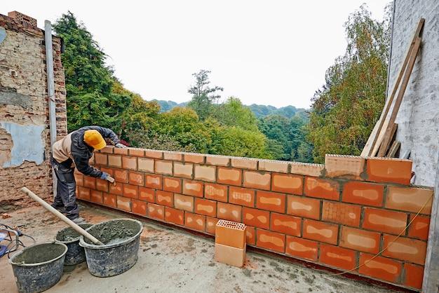 Construção de uma parede para nova sala com trabalhador Foto Premium