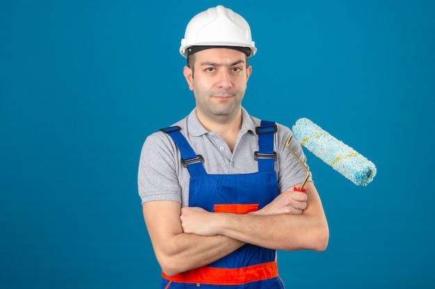 Construção, olhando seriamente o trabalhador de uniforme e capacete de segurança com as mãos cruzadas, segurando o rolo de pintura azul isolado Foto gratuita