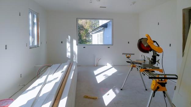 Construção que remodela em casa o corte da placa de madeira da guarnição sobre com a serra circular. Foto Premium