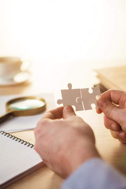 Construindo um sucesso nos negócios. mãos com quebra-cabeças Foto gratuita