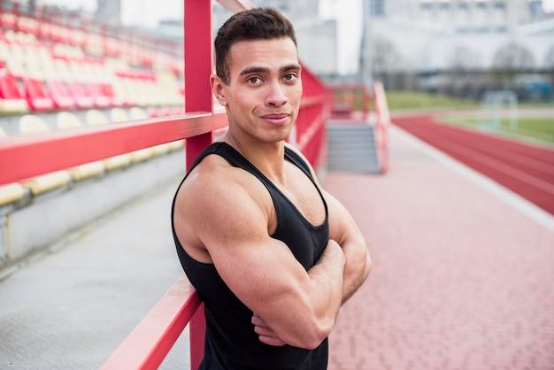 Construir atleta com o braço cruzado no atletismo do estádio Foto gratuita