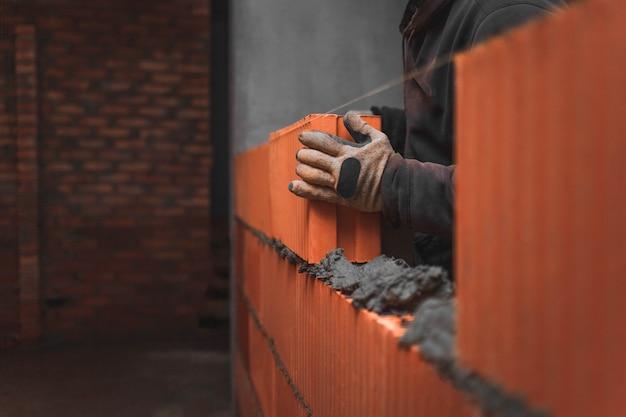 Construtor colocando um grande bloco de tijolos na argamassa, criando uma parede Foto Premium