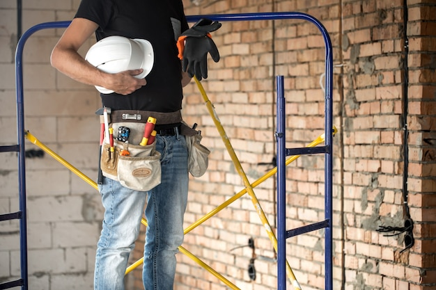 Construtor com ferramentas de construção no canteiro de obras Foto gratuita