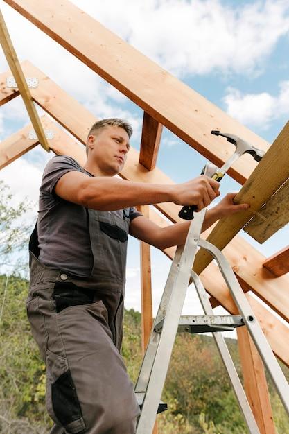 Construtor construindo o telhado da casa Foto gratuita
