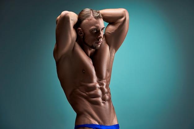 Construtor de corpo masculino atrativo no fundo azul Foto gratuita