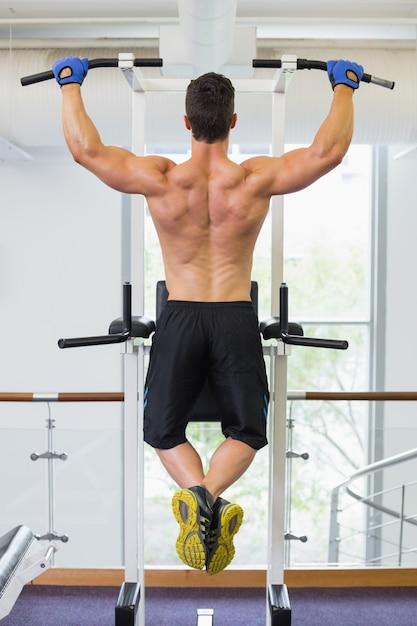 Construtor de corpo masculino fazendo pull ups no ginásio Foto Premium