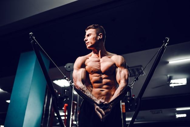 Construtor de corpo muscular malhando na academia fazendo exercícios com mosca no peito na máquina de cabos de arame Foto Premium