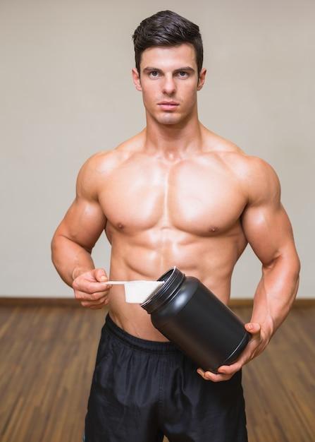 Construtor de corpo segurando uma colher de proteína mix em academia Foto Premium