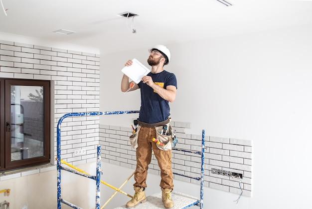 Construtor de eletricista com trabalhador de barba em um capacete branco no trabalho, instalação de lâmpadas em altura. profissional de macacão com uma broca no local de reparo. Foto gratuita