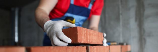 Construtor faz uma parede de tijolos em um close de casa Foto Premium