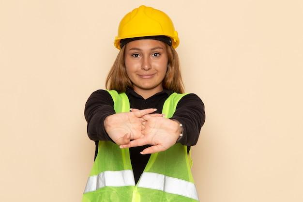Construtor feminino de vista frontal com capacete amarelo sorrindo na parede branca feminina Foto gratuita