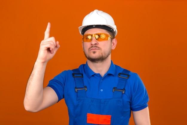 Construtor homem vestindo uniforme de construção e capacete de segurança adverte de perigo, levantando o dedo mostrando sinal de aviso com o dedo em pé sobre parede laranja isolada Foto gratuita