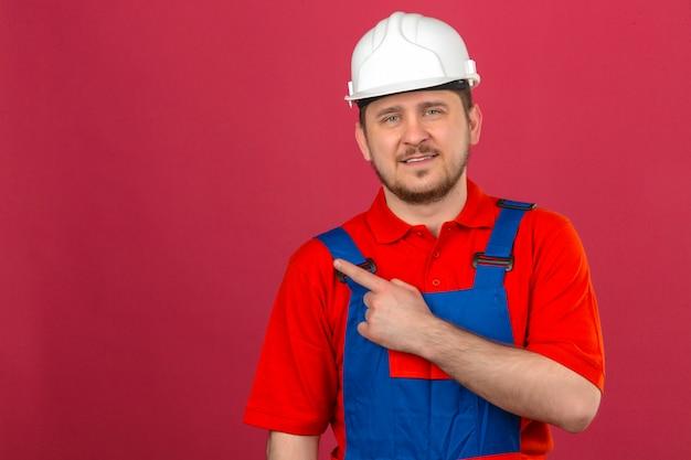 Construtor homem vestindo uniforme de construção e capacete de segurança, apontando o dedo para copiar o espaço olhando confiante em pé sobre parede rosa isolada Foto gratuita
