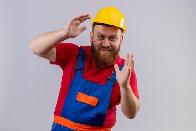 Construtor jovem barbudo com uniforme de construção e capacete de segurança mostrando gesto de tamanho com as mãos com sorriso confiante no rosto, símbolo de medida Foto gratuita