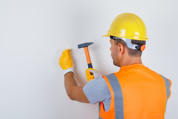 Construtor masculino de uniforme, capacete, luvas martelando o prego na parede, vista traseira. Foto gratuita