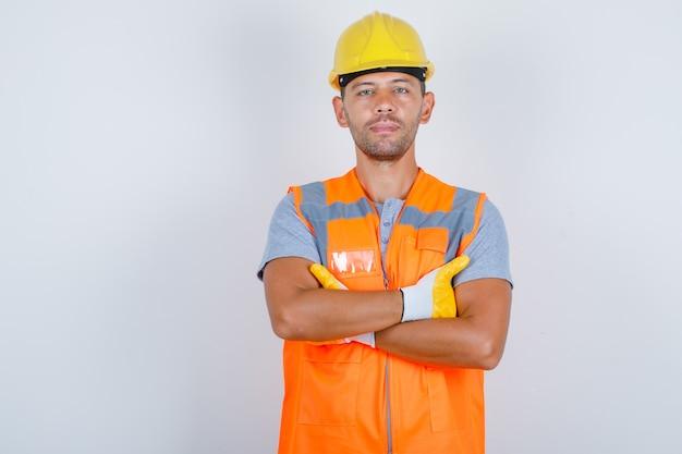 Construtor masculino de uniforme em pé com os braços cruzados e olhando confiante, vista frontal. Foto gratuita