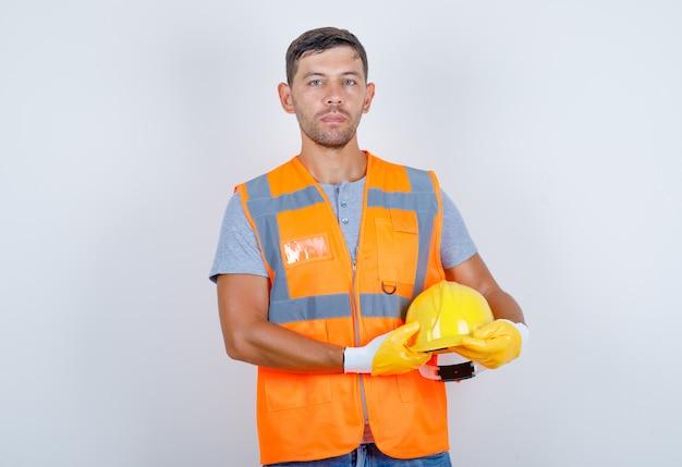 Construtor masculino de uniforme, jeans, luvas, segurando o capacete nas mãos, vista frontal. Foto gratuita