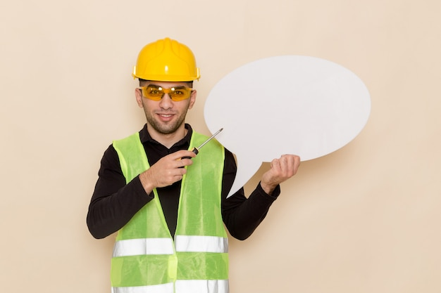 Construtor masculino de vista frontal com capacete amarelo segurando uma grande placa branca sobre o fundo claro Foto gratuita