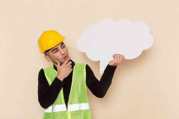 Construtor masculino de vista frontal com capacete amarelo segurando uma placa branca sobre fundo claro Foto gratuita