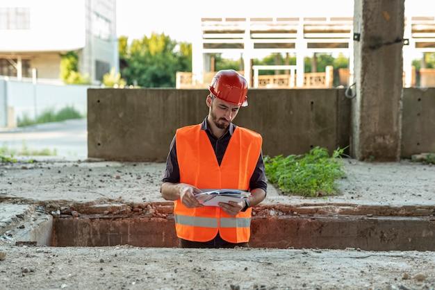 Construtor olhando documentos no canteiro de obras Foto gratuita