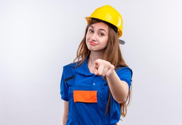 Construtora jovem com uniforme de construção e capacete de segurança, parecendo confiante apontando com o dedo indicador Foto gratuita