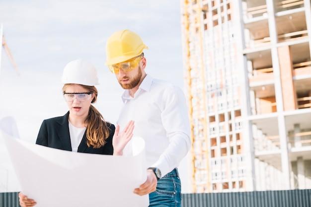 Construtores chocados olhando o rascunho Foto gratuita