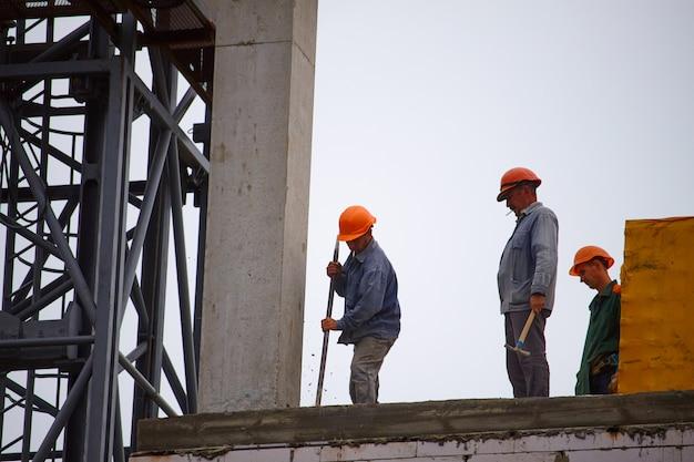 Construtores masculinos trabalham na construção de um edifício de cimento de vários andares Foto Premium