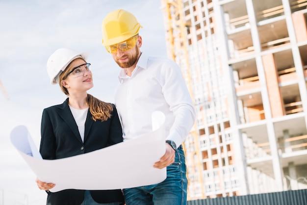 Construtores sorridentes com rascunho Foto gratuita