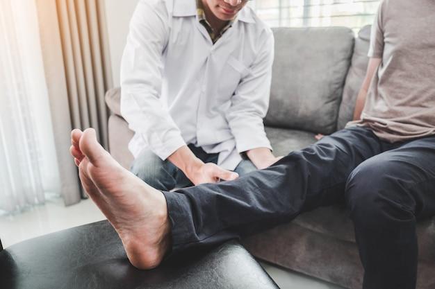 Consulta médica com paciente problemas no joelho fisioterapia visite a casa do paciente Foto Premium