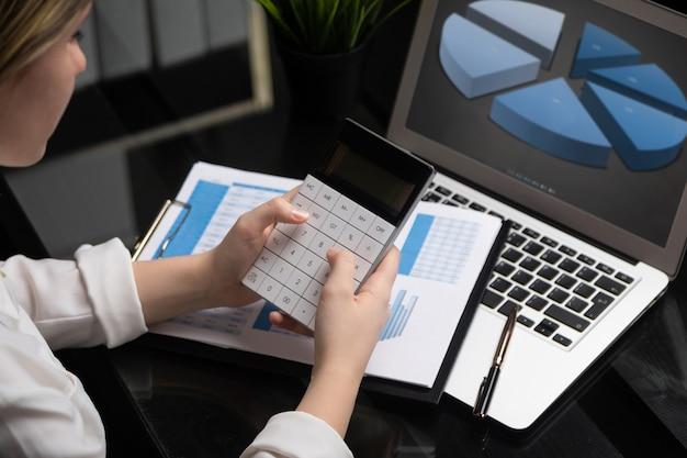 Consultor de investimento de empresária analisando a declaração de balanço anual do relatório financeiro da empresa trabalhando com calculadora e laptop Foto Premium