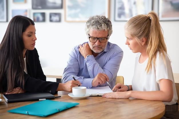 Consultor jurídico da família explicando detalhes do documento para pai adulto e filha adulta Foto gratuita