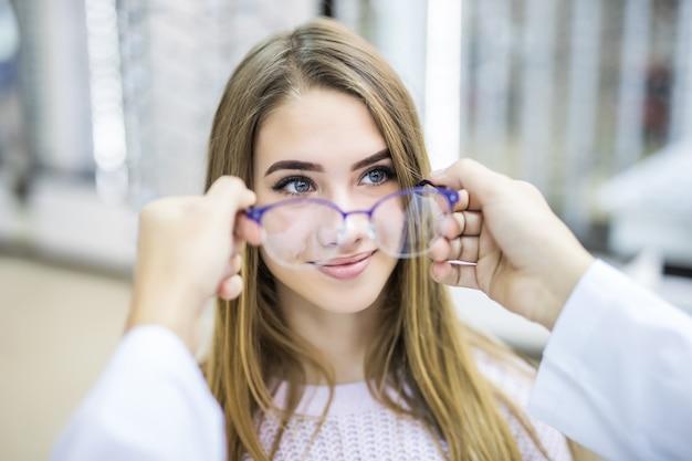 Consultor profissional ajuda seu cliente a escolher óculos médicos em loja moderna Foto gratuita