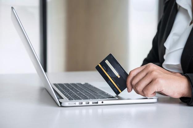 Consumidor de mulher de negócios, mantendo o cartão de crédito e digitando no laptop para compras e pagamentos on-line, faça uma compra na internet, pagamento on-line, redes e compre a tecnologia do produto Foto Premium