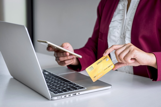 Consumidor jovem segurando smartphone, cartão de crédito e digitando no laptop para compras e pagamentos on-line, faça uma compra na internet, pagamento on-line, redes e compre a tecnologia do produto Foto Premium