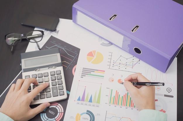 Contador com gráfico de documento financeiro na mesa do escritório. Foto Premium