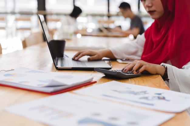 Contador de mulher de negócios muçulmano jovem vestindo hijab vermelho, trabalhando com calculadora. Foto Premium