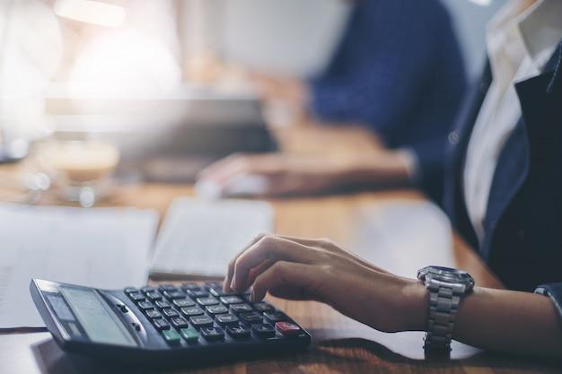 Contador de mulher trabalhando usando calculadora para calcular o relatório financeiro no local de trabalho Foto Premium