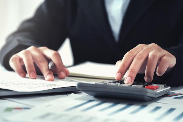 Contador usando calculadora para calcular com laptop trabalhando no escritório Foto Premium