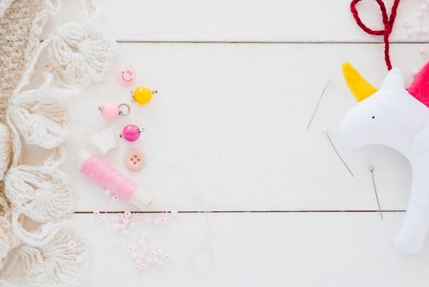 Contas coloridas; carretel; agulha e pano unicórnio na mesa de madeira branca Foto gratuita