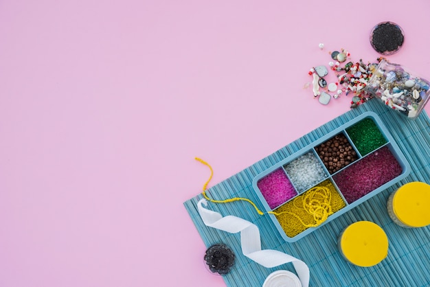 Contas coloridas; fita e miçangas no pano de fundo rosa Foto gratuita