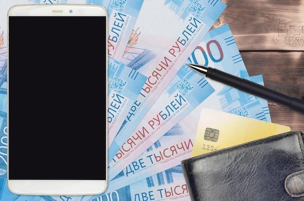 Contas de 2.000 rublos russos e smartphone com bolsa e cartão de crédito. conceito de pagamentos eletrônicos ou comércio eletrônico. compras online e negócios com uso de dispositivos portáteis Foto Premium
